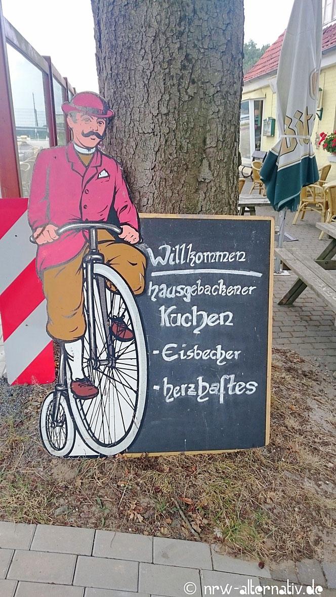 Radfahrer auf Schild mit Speisekarte am Emsradweg.