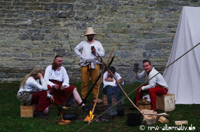 Eine Männergruppe sitzt während der Soester Fehde um ein Lagerfeuer