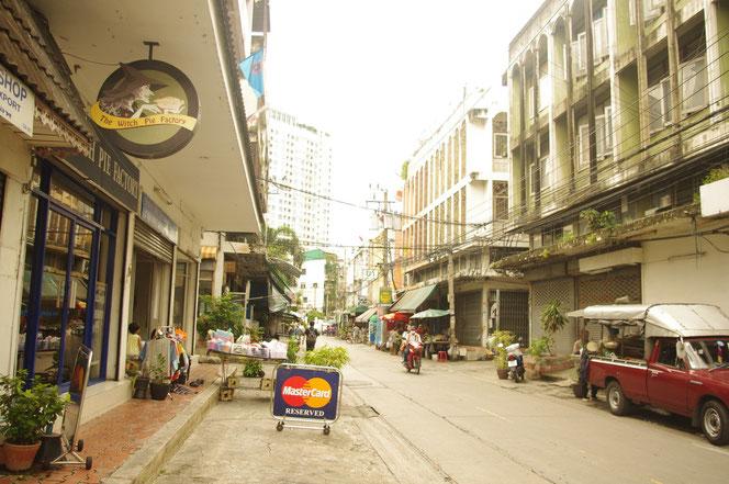 バンコクの街中の写真 中央が道路で両脇に建物。右側には路上駐車をする赤茶色のピックアップトラック。道路にはマスターカードの看板も見える。