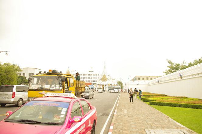バンコク王宮エリアのタクシー 写真左側にピンク色のバンコクのタクシー 右側には バンコクの歩道と白壁が写る [タイ・バンコク旅行ブログの写真]