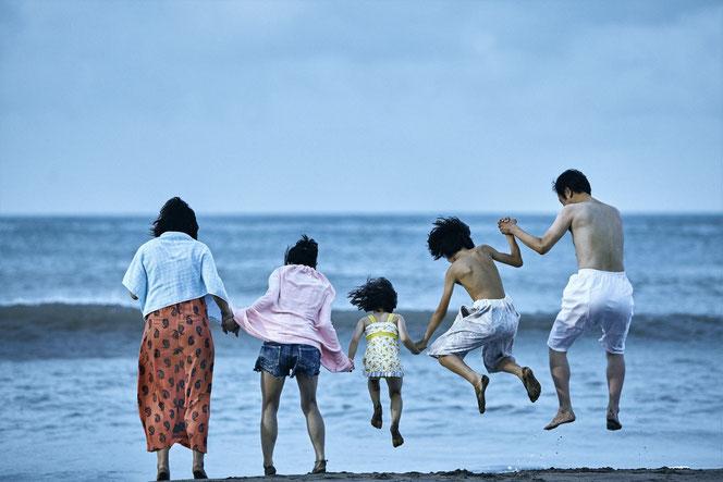 La petite fille est heureuse dans sa nouvelle famille, qui l'emmène à la plage (©Le Pacte).