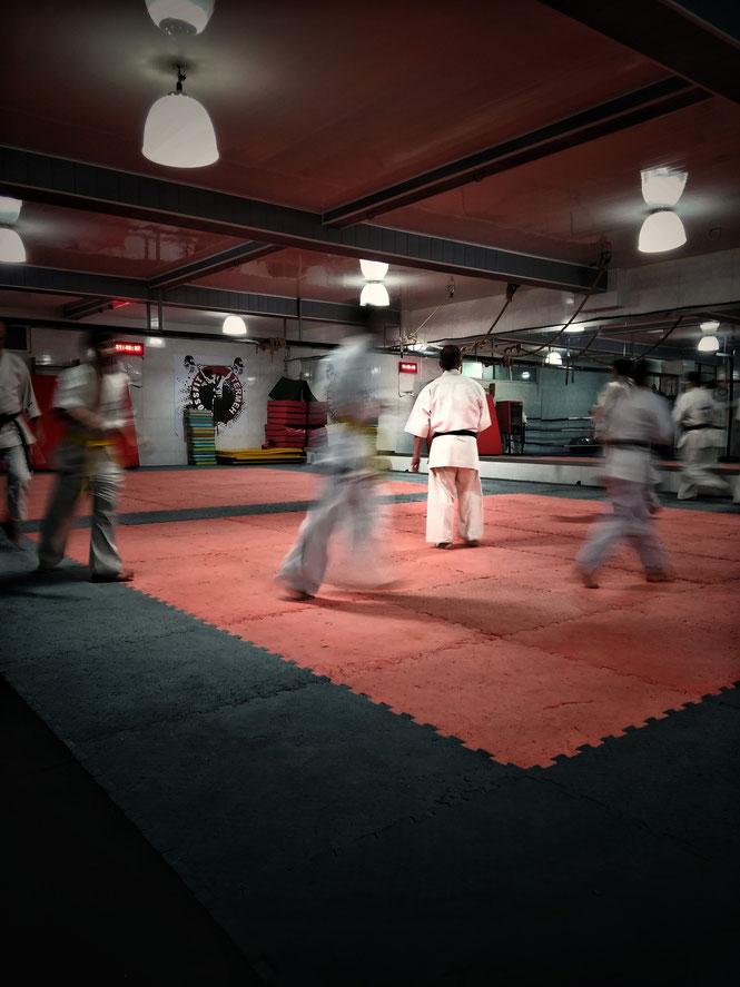 Karate-Schüler trainieren in einer Sporthalle und laufen im Kreis, um sich zu erwärmen und um sich auf das Training vorzubereiten.