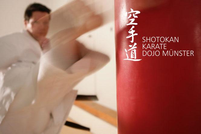 Karate-Meister tritt mit einem Roundhouse-Kick vor einen Boxsack.