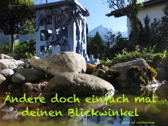 Die Alpspitze gespiegelt in der Wasseroberfläche des Gartenteiches mit der Beschriftung: Ändere doch einfach mal deinen Blickwinkel