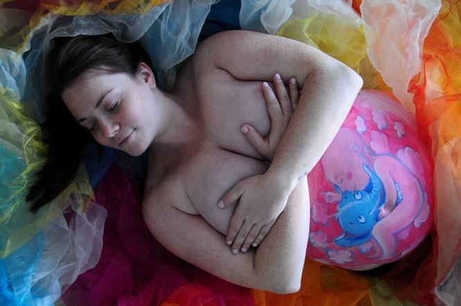 Mit gekreuzten Armen verdeckt die Schwangere ihre Brüste. Ein Lächeln verzaubert ihr Gesicht. Sie liegt mit geschlossenen Augen in diesem Farbenmeer. Der Bauch ist bemalt mit rosa Wölkchen, einem Baby, das einen himmelblauen Elefanten an sich drückt.