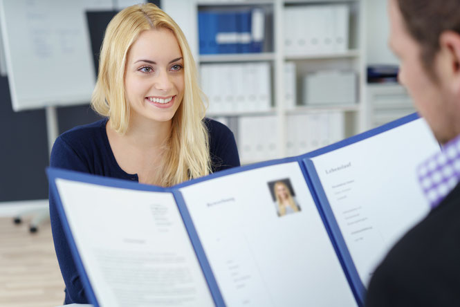 Junge Frau beim Vorstellungsgespräch, Arbeitgeber liest Bewerbungsmappe