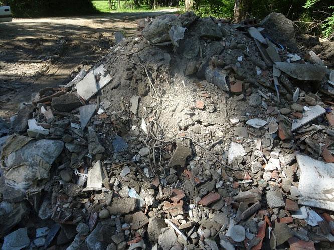 Poussé contre le lit du ruisseau à Oloron divers déchets : plastiques, amiante, etc...