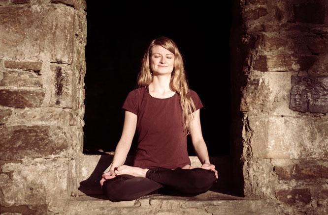 Auf dem Bild sieht man eine meditierende Person im Sonnenlicht.