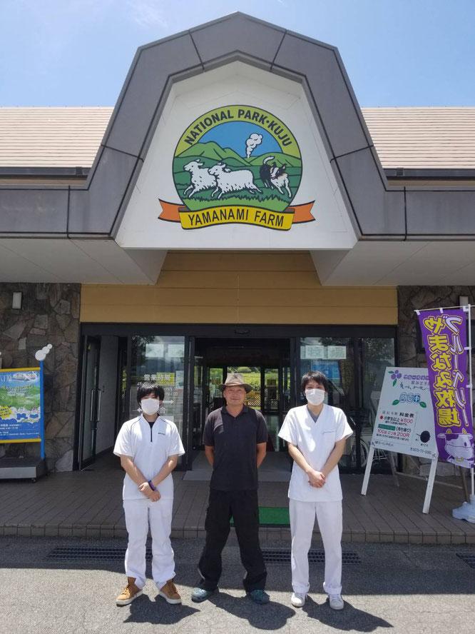 安部代表(中央)と観光牧場入口の写真