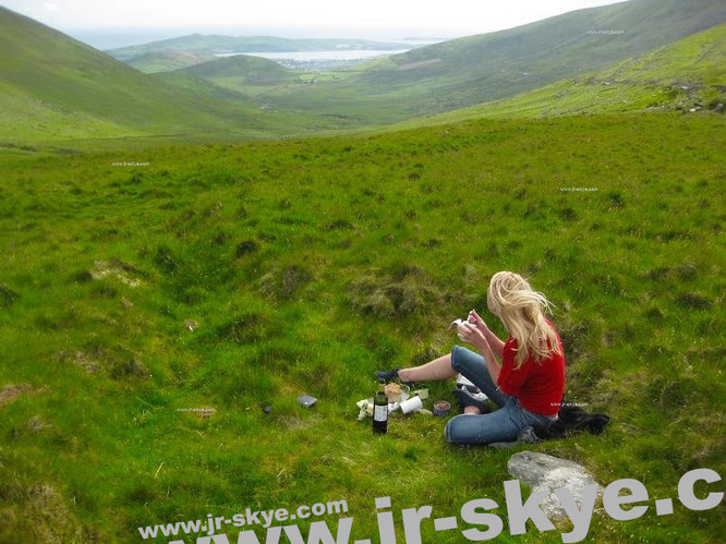 """With Mona-Liza: drinking red wine at Conor Pass, Republic of Ireland (52° 10′ 55″ N, 10° 12′ 26″ W)."""