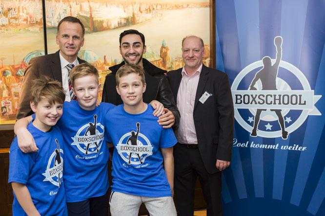 Staatsrat Christoph Holstein (links), Bronze-Medaillen-Gewinner Artem Harutyunyan und Olaf Jessen, Vorsitzender der Boxschool, mit drei Schülern (Foto: Matthias Scharf)