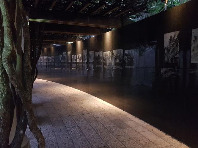 Der geschwungene Gang mit der Granitwand und den Bildern über den Holocaust