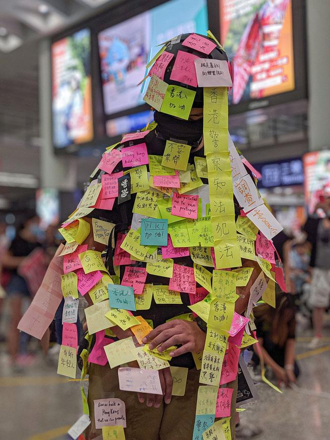 身体に香港抗議デモに関するメッセージが書かれたポストイットを貼り付けるレノン・マン。