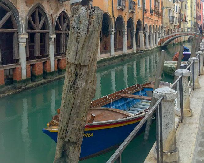 Gondeln und Boote in einem kleinen Kanal in Venedig