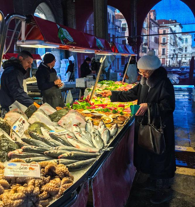 Frau kauft frischen Fisch auf dem Rialtomarkt in Venedig