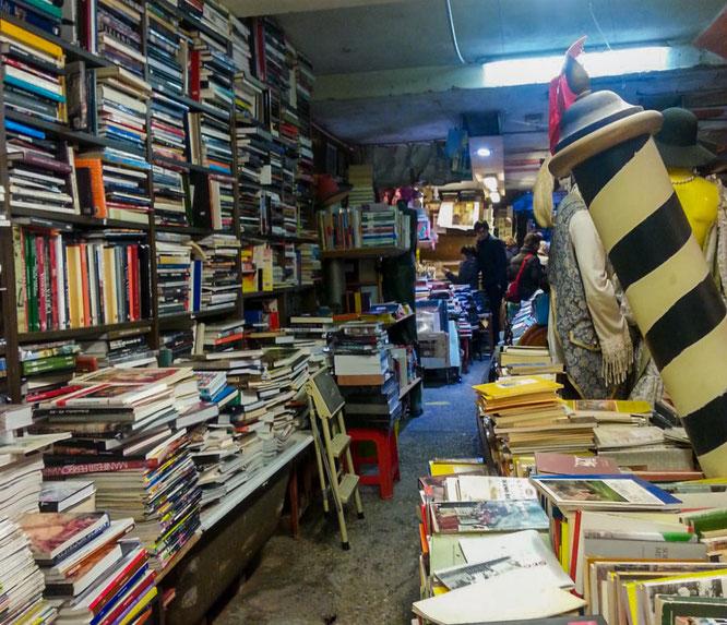 Viele Bücher und Postkarten in Badewannen und Regalen in dem Buchladen Liberia Acqua Alta in Venedig