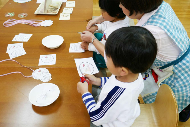 幼稚園児クラスのモンテッソーリ活動で母の日のプレゼントに、年少児が、丸い形を慎重にハサミで切り抜いています。