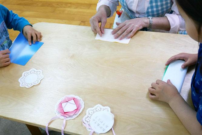 幼稚園児クラスの年長児が、モンテッソーリ活動で母の日のプレゼントにペンダントを製作。ペンダントにつけるカーネーションを折り紙で作っています。