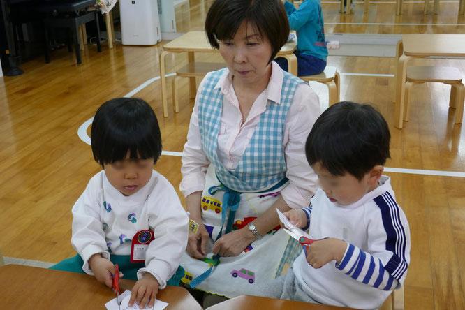 幼稚園児クラスのモンテッソーリ活動で、年少児が母の日のプレゼントにペンダントを製作しています。