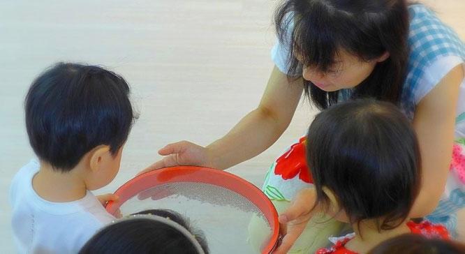 1歳児がオーシャンドラムに触れて音を出しています。よく集中しています。