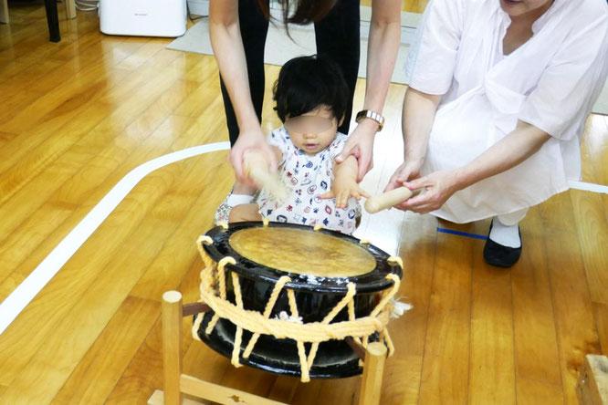 10ヶ月の生徒がバチを握って太鼓を一生懸命叩こうといしています。子どもの中に、リズムに対する強い興味や音楽性が培われていることがわかります。