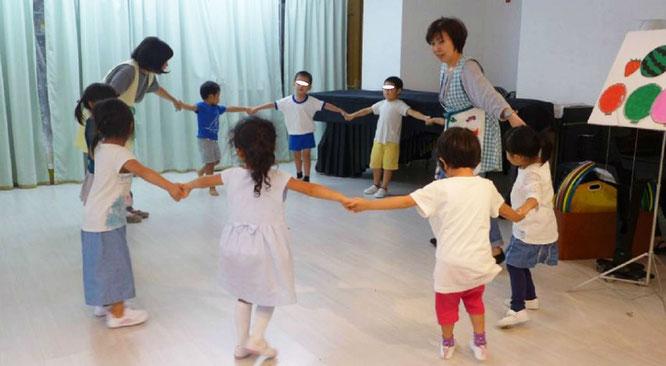 リトミックの活動で、幼稚園児クラスの生徒がみんなで輪を作って身体を楽しそうに動かしています。