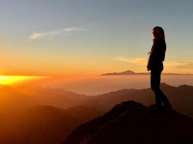 Person auf dem Berg mit Weitsicht im Sonnenuntergang  - Jahrestraining
