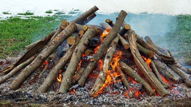 Bereits in den frühen Morgenstunden wird das Holzfeuer entzündet, damit die Glut um die Mittagszeit gerade recht ist.
