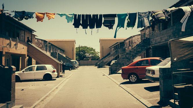 Der äußere Zufahrtsbereich zu den sehr einfach gemauerten Hostels. Dennoch sind gemauerte Häuser hier natürlich Luxus. Wo auch immer man hinschaut Wäsche – für mich ein Zeichen des nicht Aufgebens - Township Langa Cape Town South Africa