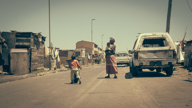 Typisches Straßenbild aus Bretter- und Blechhütten neben einfachen Backsteinbauten. Hier wird alles genutzt und auch die Autos haben eine weitaus höhere Lebensdauer als in Europa - Township Langa Cape Town South Africa