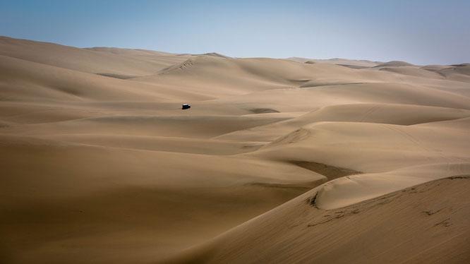 Fahrzeuge lassen die Größendimensionen in endlose Weite der Dünen der Namib erahnen...