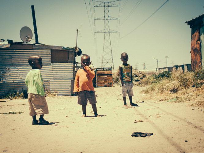 Drei Jungs im ärmsten Teil von Langa. Hier kommen die Neuankömmlinge an und versuchen sich behelfsmäßig eine Hütte in direkter Nachbarschaft zur Flughafenautobahn zu bauen. Auch im Township sind Zuwanderungsprobleme auf knappem Raum immanent.