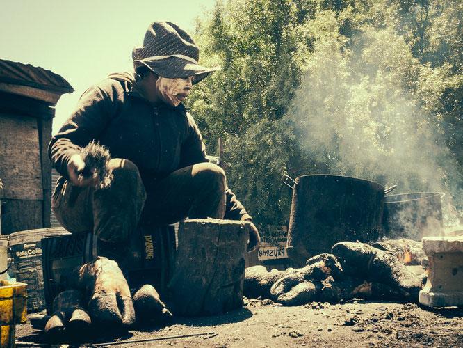 Nichts wird weggeworfen, die Hufe toter Tiere werden verkohlt, um Haut und Fett abzuziehen bevor es an die Weiterverarbeitung geht. Das Fett der Tiere dient als weißer Hautschutz vor dem Qualm des Feuers und der Dämpfe - Township Langa Cape Town