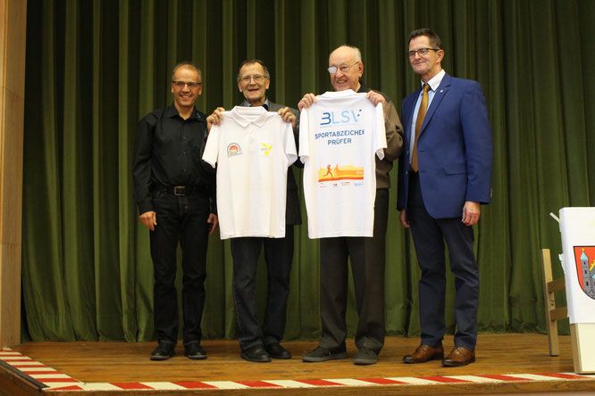"""Klaus Greier übergibt zusammen mit Peter Suckfüll das """"Sportabzeichen-Prüfer""""-Polohemd an Herbert Langenbrunner und Wolfgang Taubert."""