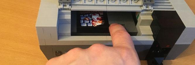 """Wie beim Original: Die """"Super Mario Bros.""""-Cartridge aus LEGO wird im gefederten Frontlader-Schacht verstaut und nach unten gedrückt. Elektronik steckt allerdings keine unter der Chassis"""