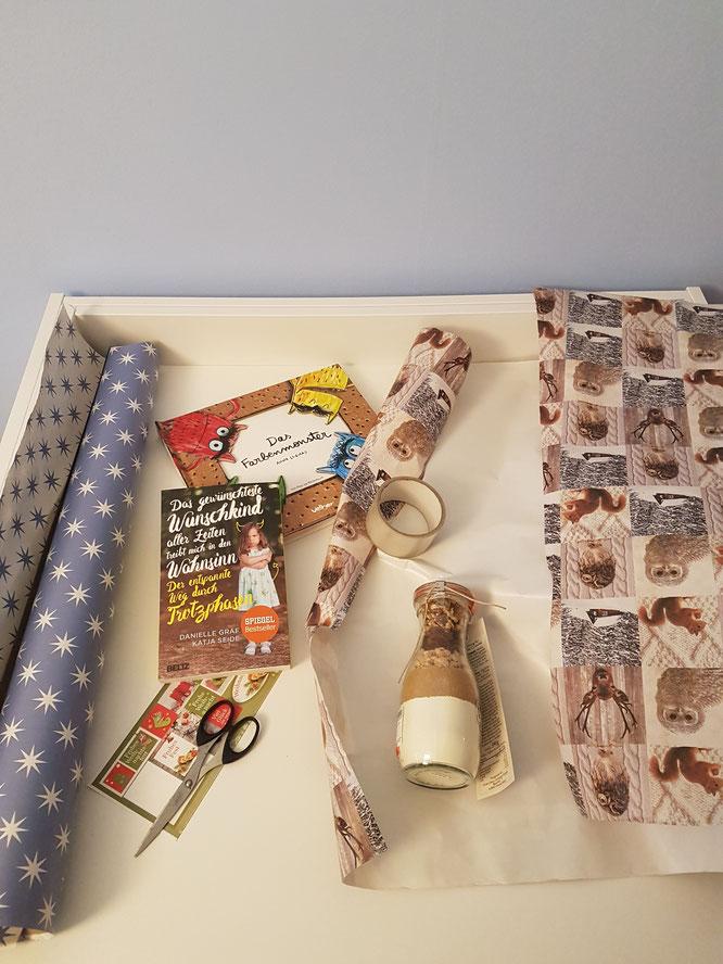 Weihnachtsgeschenke werden auf weißem Tisch verpackt. Geschenke-Guide für Mamas auf Patschehand.de.