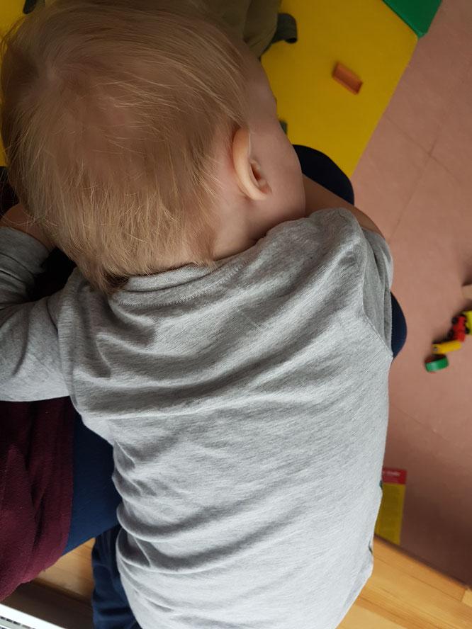 Kleinkind in Kita auf Jana Mama Patschehands Schoß.