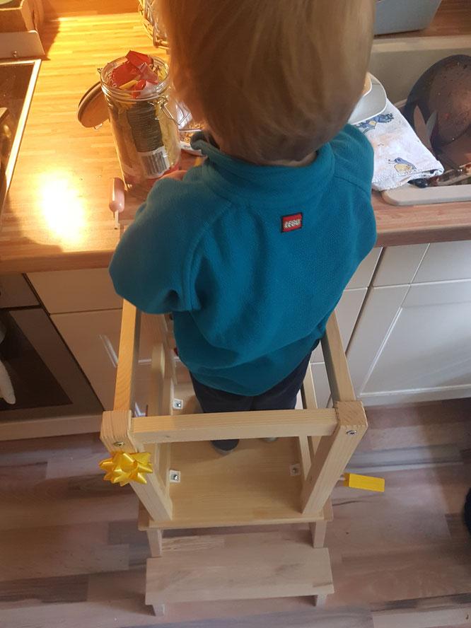 Kleinkind im Montessori-inspirierten Learning-Tower in der Küche im Hause Patschehand.