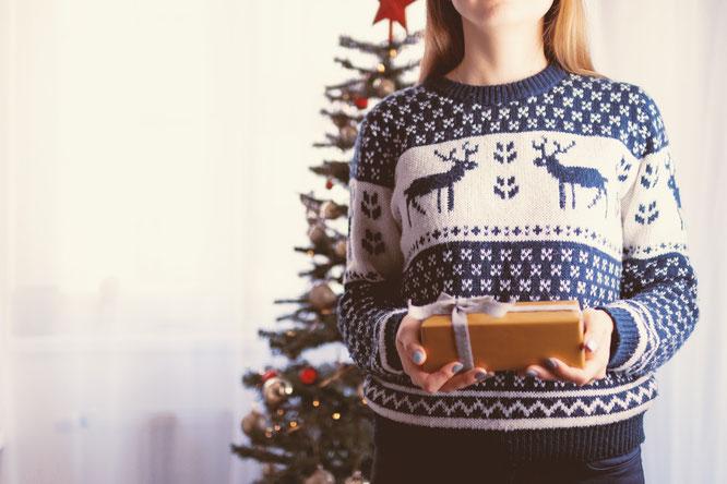 Junge Frau mit Weihnachtsgeschenk vor Tannenbaum: Symbolbild für Patschehands Mama-Geschenke-Guide.