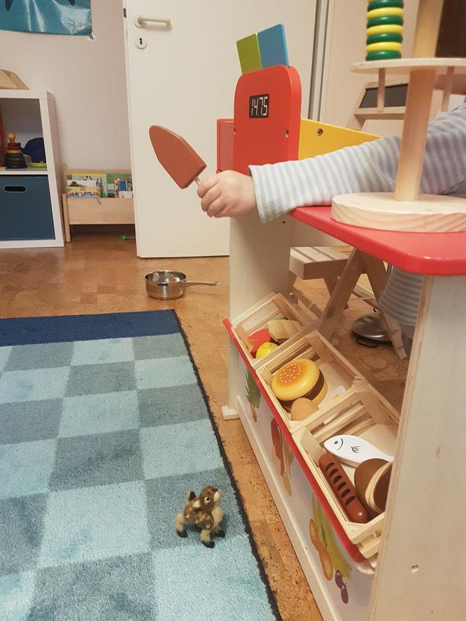 Kleinkind spielt mit Kaufmannsladen im Kinderzimmer. Tipps für den Kauf auf Mama-Blog Patschehand.de.