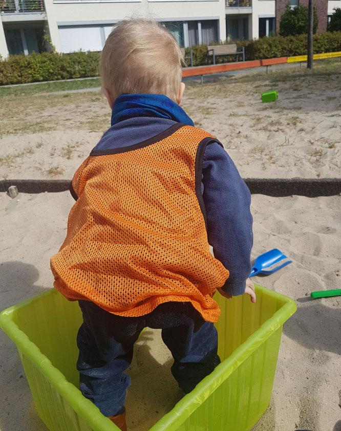 Kleinkind spielt im Sandkasten der Kita während der Eingewöhnung.
