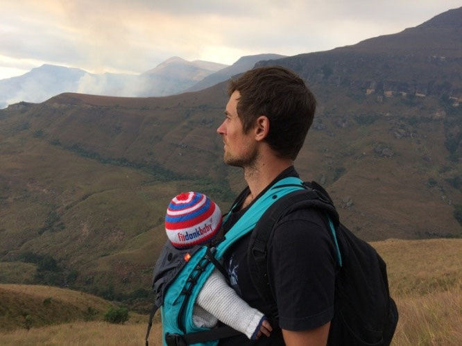 Frischgebackener Vater mit Baby in Komforttrage auf Reisen in Afrika.