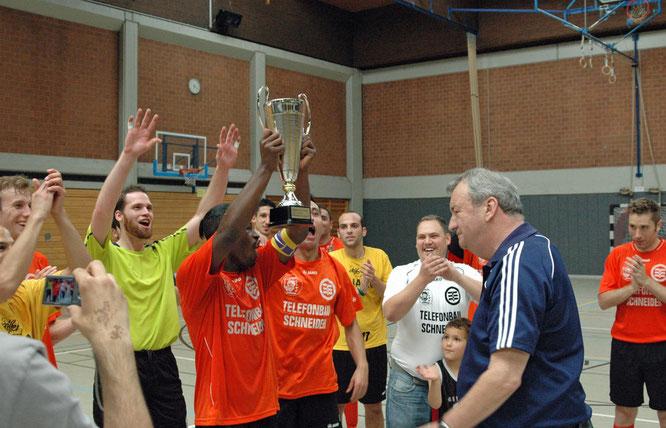 "FVN-Ausschussmitglied Manfred Neufeld überreicht den neuen FVN Futsal-Wanderpokal an ""Lions""-Kapitän Carlos Penan (Foto: Gött)"