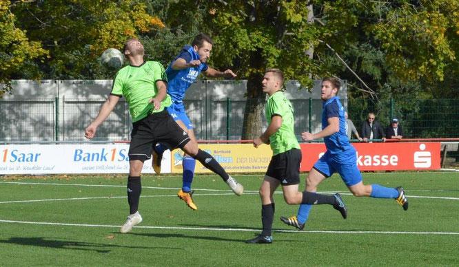 Christian Scheid (blau) im Kopfballduell. Rechts läuft Julian Linnenbach, ebenfalls blau.