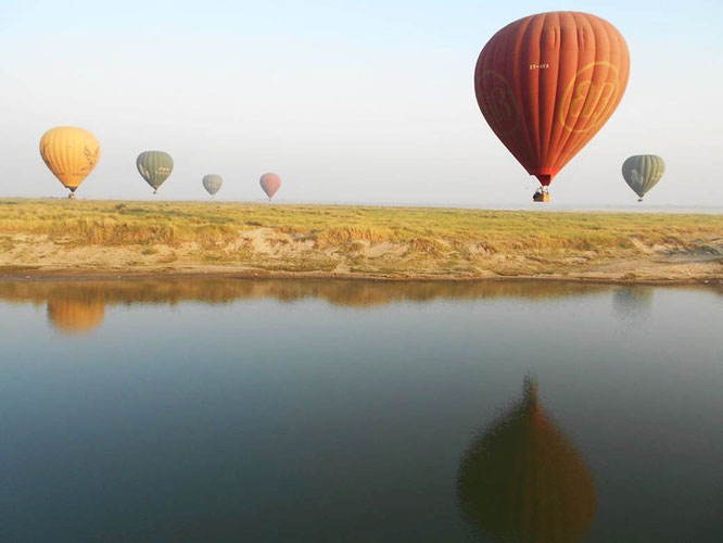 Hot air balloons over river in Bagan