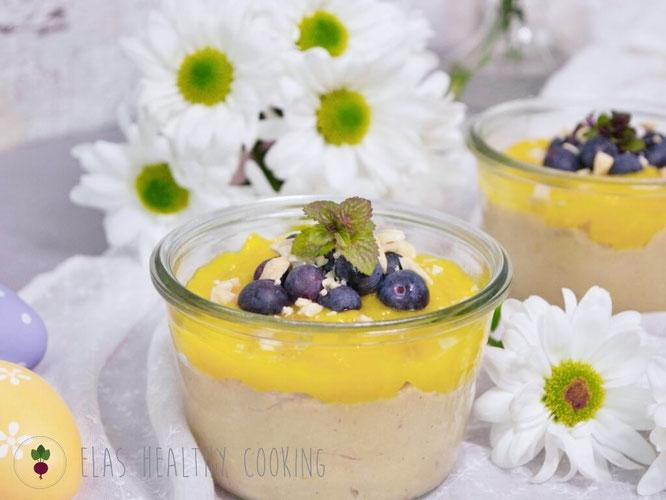 Veganer Hirsepudding im Glas mit Mangopüree, Heidelbeeren und gehackten Nüssen