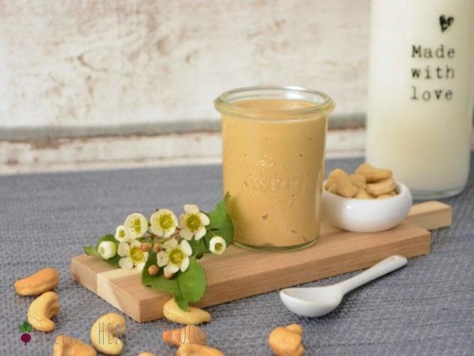 Cashewmus im Glas auf Holzbrett mit Milchflasche