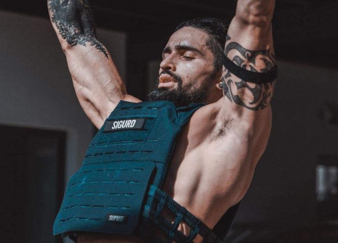 Mann macht Klimmzüge mit Gewichtsweste