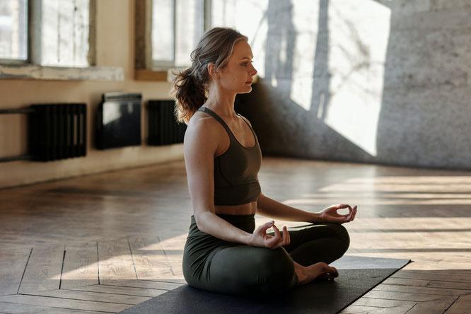 Frau übt Körperwahrnehmung beim Yoga