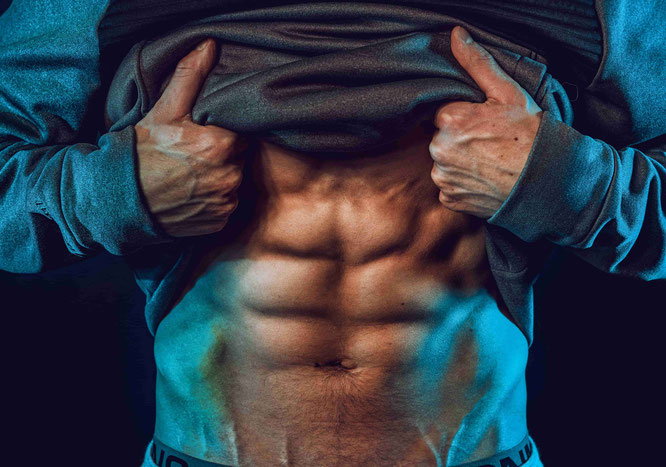 Mann zeigt seine Bauchmuskeln